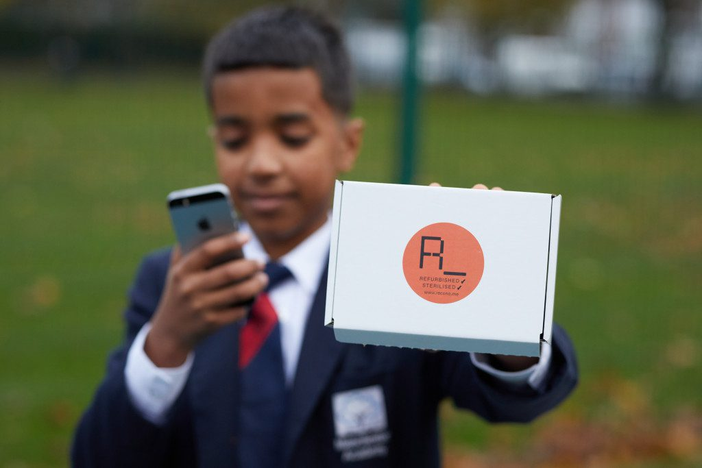 A school boy holding a Refurbished Mobile phone